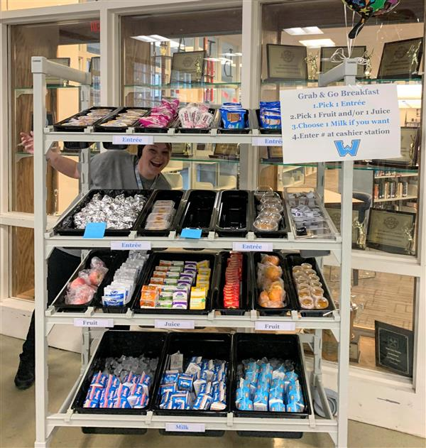 Watauga High School Child Nutrition Staff Member Samantha Brown peeks through the shelves of a new breakfast kiosk at the WH