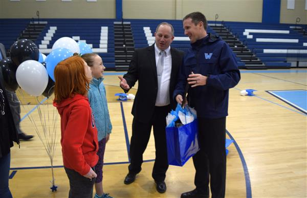 Watauga County School Superintendent Dr. Stephen Martin congratulates Blanton while Blanton's child