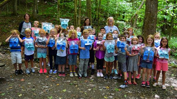 Cove Creek Second Graders pose with their new shoes beside the creek.