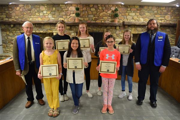 A group of students were recognized by the school board after winning a handwriting contest.