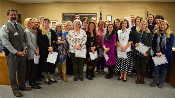 A large group of teachers who were award WEF grants pose with board member at the meeting.