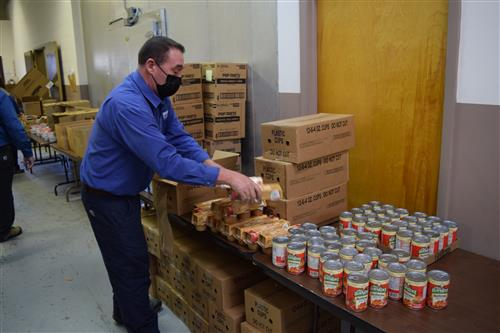Randy Woodring helps to load food donated from Lowes Foods in Boone to send home with students over Christmas break.