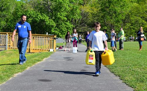 Green Valley fifth-grader Jay Terzaken tries his hand at carrying five gallon jerry cans of water.