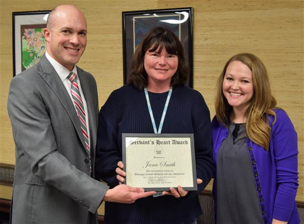 Scott Elliott and Tiera Stark present an award to Jana Smith at the central office.