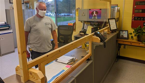 David Cook puts the final touches on a plexiglass screen in the Cove Creek School office.