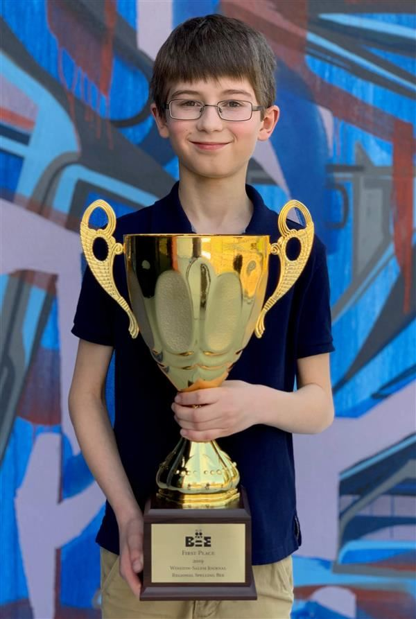 Sam Nystrom poses with his trophy after winning the regional spelling bee.