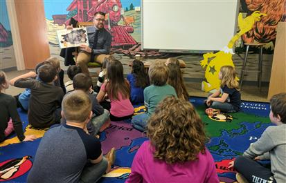 WCS Instructional Services Director Ike Smith reads to a first grade class at Mabel School.