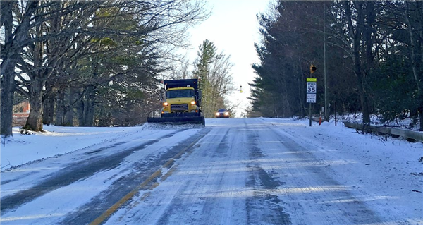 A Department of Transportation truck plows a snowy road near Parkway School.